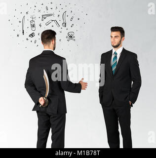 Ruthless businessman handshake with hiding a weapon and weapon symbols around his head - Stock Photo