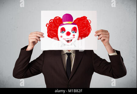 Young businessman holding a cardboard with a clown on it in front of his head - Stock Photo