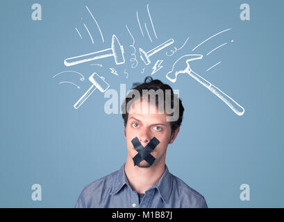 Young man with taped mouth and white drawn beating hammer marks around his head - Stock Photo