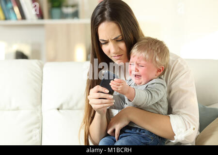 Baby having a tantrum and fighting with his mother for a smart phone sitting on a couch in the living room at home - Stock Photo