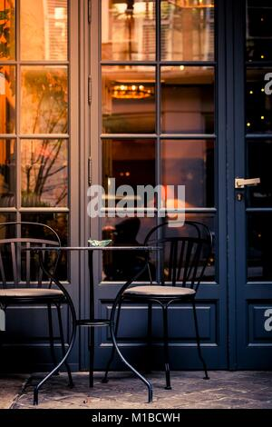 Small wrought iron table and chair on a street outside a cafeteria window and glass door with warm glowing reflections - Stock Photo