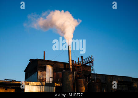 factory emits steam-smoke water in the blue sky - Stock Photo