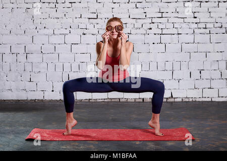 Young attractive smiling woman practicing yoga. Sporty pretty woman loves sports. - Stock Photo