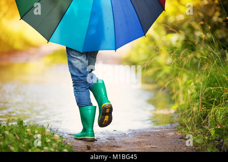 Child walking in wellies in puddle on rainy weather - Stock Photo