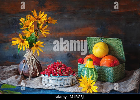 Beautiful autumn still life from different pumpkins in a wicker basket, yellow daisies in a clay ceramic brown ethnic - Stock Photo