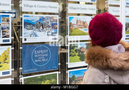 Woman looking in Estate Agents window, buying a property, in England, UK. - Stock Photo