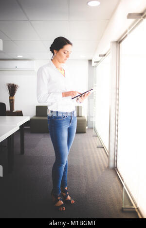 Beautiful brunette business woman standing in a boardroom working on a tablet computer - Stock Photo