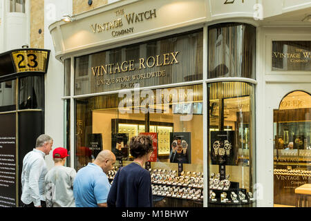 Peple looking at vintage watches through shop window of The Vintage Watch Company, Burlington Arcade, London, UK - Stock Photo
