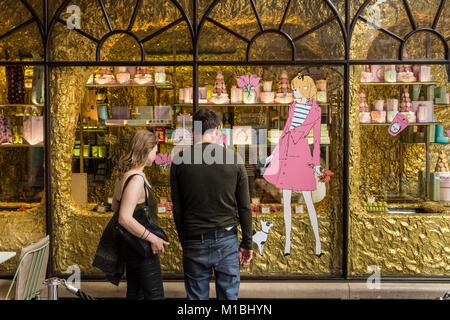 Young couple looking through the window of upmarket bakery Ladurée in Burlington Archade in London, UK - Stock Photo