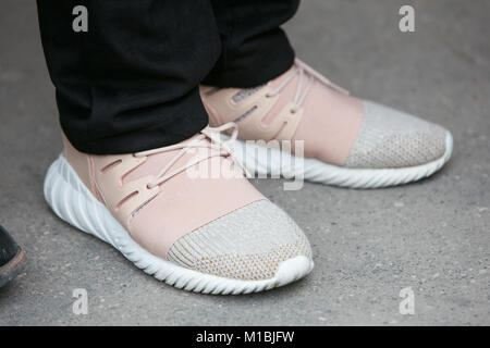 MILAN - JANUARY 15: Man with pink and white sneakers and black trousers before Fendi fashion show, Milan Fashion - Stock Photo