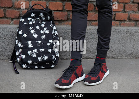 MILAN - JANUARY 15: Man with black Dior backpack with white mosquitos and red and black Dior shoes before Fendi - Stock Photo