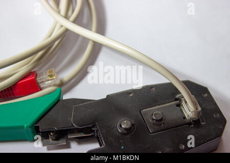 Network LAN cable cord crimper pliers with cable on the white background. Crimping tool. - Stock Photo