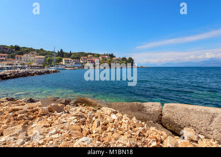Rocky coast of Ionian Sea and houses on the hill in distance. Kassiopi village in Corfu. Greece - Stock Photo