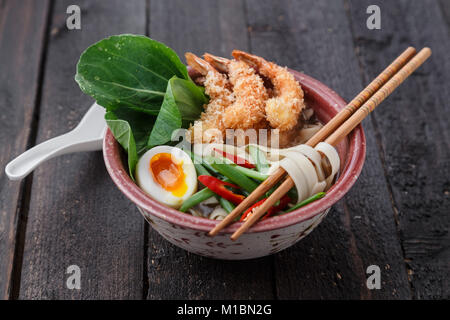 Asian spicy seafood noodle soup with tempura shrimp and greens, close view - Stock Photo