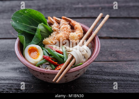 Japanese noodle soup topped with tempura shrimps, egg and greens, close view - Stock Photo