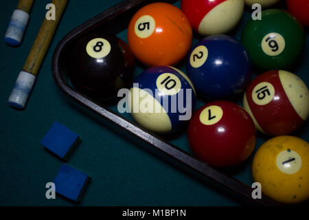 Top view of billiard balls, cue sticks, chalk on green billiard table, cinematic photo - Stock Photo