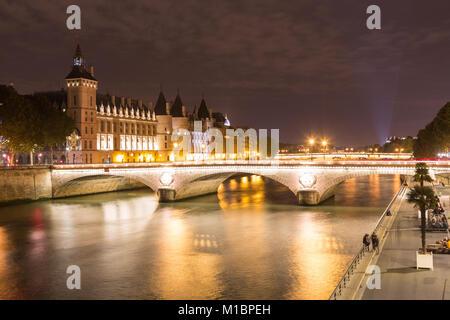 Conciergerie and Pont au Change on the banks of the Seine at night, Île de la Cité, Paris, France - Stock Photo