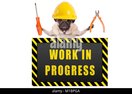 pug dog wearing yellow constructor safety helmet,holding pliers and screwdriver, with warning sign saying work in - Stock Photo