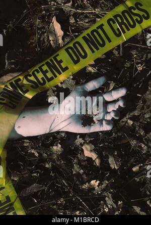 Crime scene - dead hand holdimg an oak leaf , wrapped in crime scene tape - Stock Photo