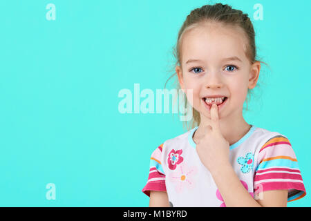 Adorable little girl smiling and showing off her first lost milk tooth. Cute preschooler portrait after dropping - Stock Photo