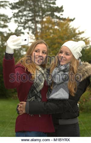 Zwei froehliche Teenager Maedchen machen mit dem Smartphone ein gemeinsames Selfie in der herbstlichen Natur. - Stock Photo