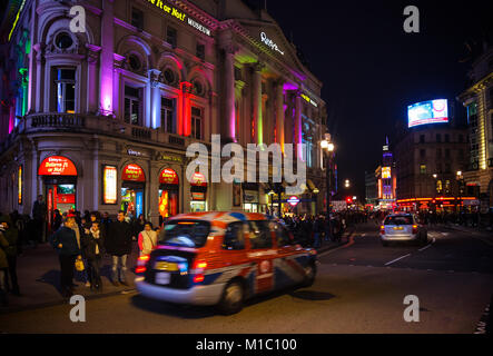 LONDON, UK - OCTOBER 30, 2012: Taxicab moves along illuminated Ripley's Believe It or Not! Museum at Piccadilly - Stock Photo