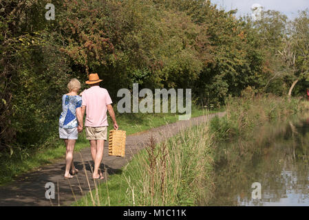 Couple carrying a picnic basket walking along a towpath next to the river - Stock Photo