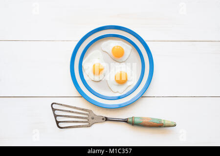 Fried Quail Eggs on a cornishware plate with a vintage spatula from above - Stock Photo