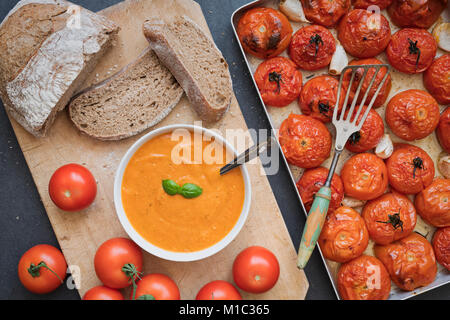 Homemade tomato and basil soup with rye bread next to roasted tomatoes and garlic in a baking tray on a slate background. - Stock Photo