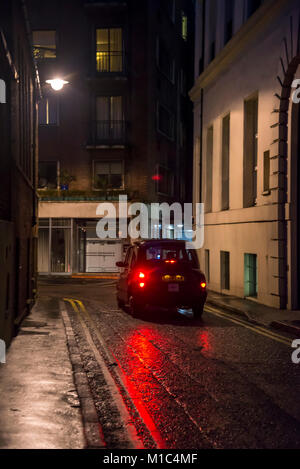 Black cab in a street in Mayfair at night, City of Westminster, London, England, UK - Stock Photo