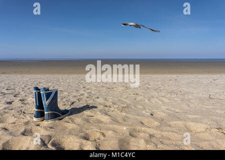 Empty beach with gull and rubber boot - Stock Photo