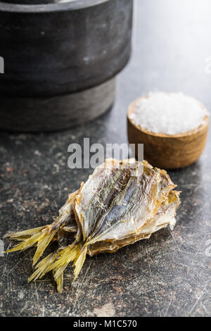 Dried salted fish on old kitchen table. - Stock Photo