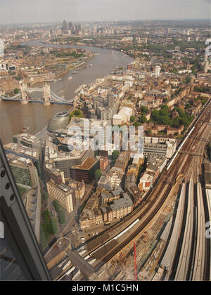 A view looking down from the top viewing floor of The Shard, London, to the train tracks and trains coming into - Stock Photo