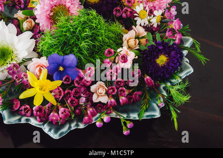 Assorted Spring Flowers on Dark Table, including Violets, Dafodils, Chrysanthemums, Waxflowers, Roses, and Chamomile. - Stock Photo