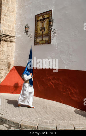 Penitent of the brotherhood of 'La Hiniesta' on the way to his church before leaving in procession. - Stock Photo