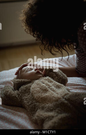 Mother looking at her baby while sleeping - Stock Photo