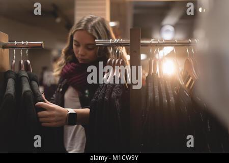 Beautiful woman selecting dress from rack - Stock Photo