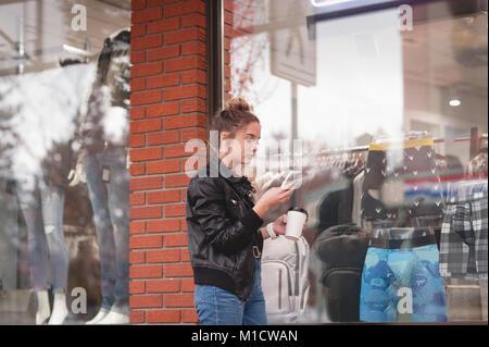 Beautiful woman using mobile phone while having coffee - Stock Photo