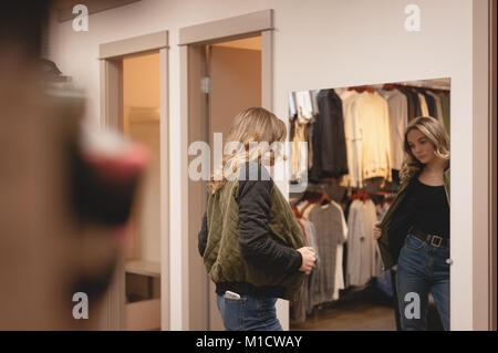 Rear view of woman checking jacket - Stock Photo