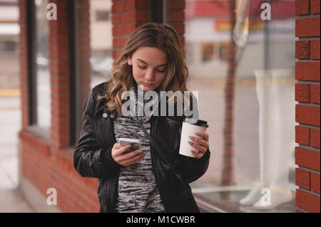 Beautiful girl using mobile while having coffee - Stock Photo