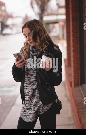 Beautiful girl using mobile while having coffee - Stock Photo
