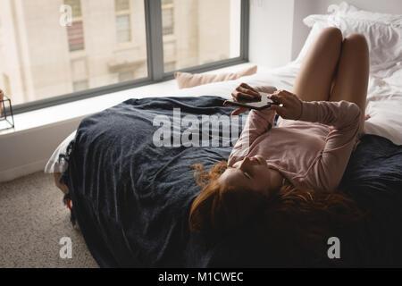 Woman using digital tablet in bedroom - Stock Photo
