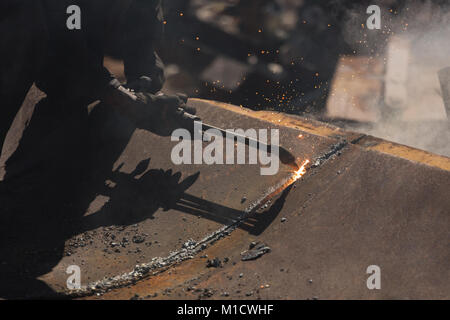 Worker cutting the metal in the scrapyard - Stock Photo