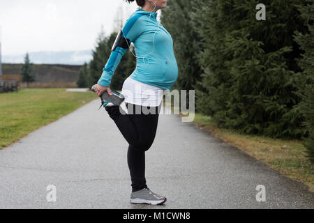 Pregnant woman performing stretching exercising - Stock Photo