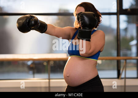 Pregnant woman practicing boxing in living room - Stock Photo