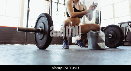 Young muscular woman clapping hands with chalk powder, preparing for barbell training in gym. Young athlete getting - Stock Photo