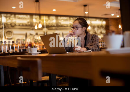 Female executive using laptop while having wine