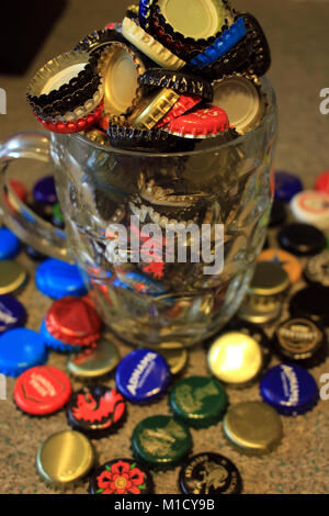 Used beer bottle tops collected after the beer has been drunk and are over flowing from a dimpled pint beer jug - Stock Photo