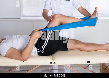 Physiotherapist Helping Patient While Stretching His Leg - Stock Photo