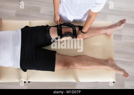 Female Physiotherapist Fixing Knee Braces On Man's Leg In Hospital - Stock Photo